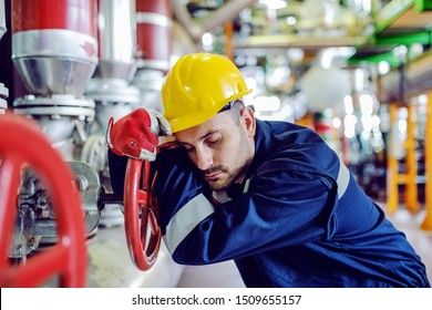 Hardworking caucasian worker in working clothes leaning on big valve and sleeping. Night shift. Energy plant interior.