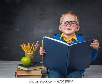 c34f47fc0eb2 Hardworking child is reading book for getting knowledge. Boy with big book  in his hands