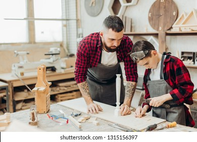 Hardworking little boy is busy taking measure and marking of wooden plank with a pencil with his father working as carpenter sitting in wooden workshop with other instruments.