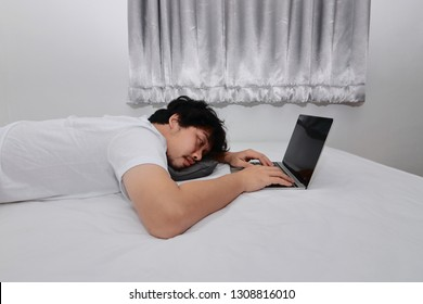 Hardworking people concept. Tired overworked young Asian man sleeping with computer laptop on the bed in bedroom.