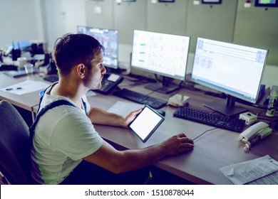 Hardworking plant worker sitting in control room, holding tablet and using computer for monitoring.