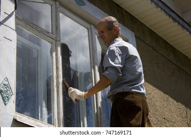 the hard-working retiree cleans the old window in the house