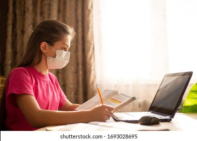 Hard-working school learner girl in medical mask, holding book, having online lesson at home, communicating with teachers, classmates, doing tasks at the computer