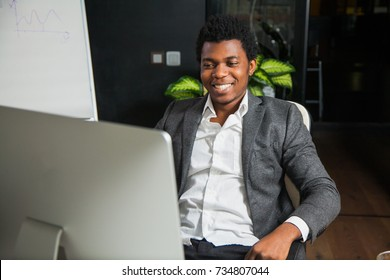 Hardworking smiling afroamerican at office look at computer monitor. Young handsome black man student do his job