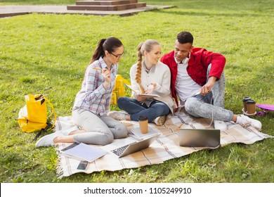 Hard-working undergraduates. Three hard-working undergraduates preparing sociology presentation while sitting outside near university