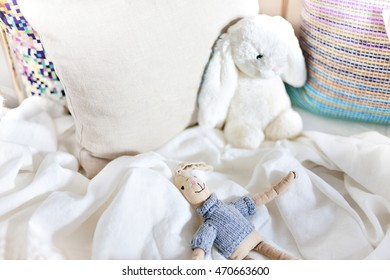 Hare toy dolls on a bed with pillows closeup including small rabbit with dress and a white wool rabbit laying to a pillow