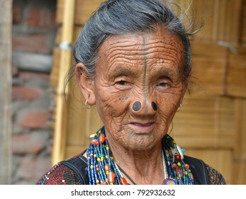 HARI, ZIRO VALLEY, INDIA - OCT 23, 2017: Old Indian tribal Apatani woman with black wooden nose plugs (yaping hullo) and distinctive tribal face tattoo at Hari village, on Oct 23, 2017.