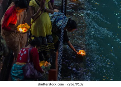 Haridwar, India - March 20, 2017:  Holy ghats at Haridwar, India, sacred town for Hindu religion. Pilgrims offering floating flowers and burning candles to the Ganges River.