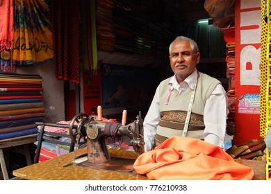 Haridwar, India - November, 6th, 2017. Man sew clothes on sewing machine in his workshop at local market near the Har Ki Pauri in Haridwar.