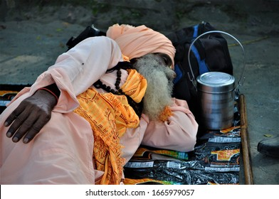 Haridwar, India - September 27 2011: dressed in shades of orange, an ascetic lies sleeping at the sacred Hindu pilgrimage site of Haridwar, India, his walking stick and tiffin nearby