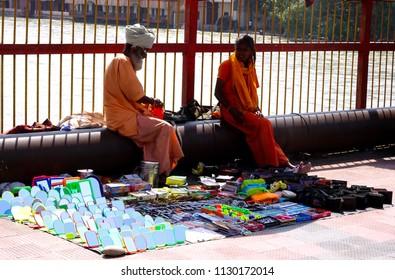 Haridwar, Uttarakhand / India - 24th May 2018 : A Hindu monk and a nun at a street side stall in Haridwar near Har Ki Pauri selling cosmetics purse mirror etc.