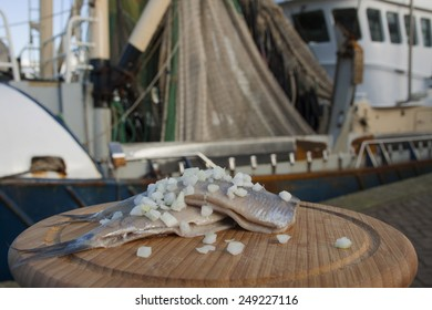 Haring with onion on a wooden plate with fishing boat