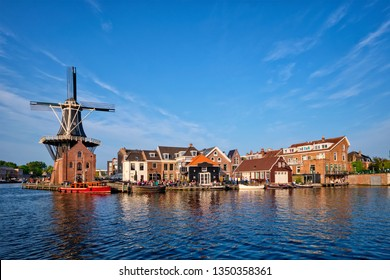 Harlem cityscape - landmark windmill De Adriaan on Spaarne river with boats. Harlem, Netherlands