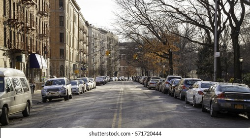 Harlem street with apartment buildings and parked cars