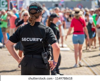Harlingen, The Netherlands - august 5 2018: A female security guard keeps an eye on the public during the Tall Ships Races Harlingen.
