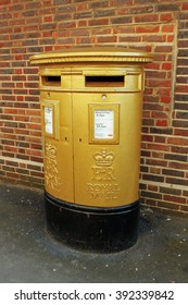 HARLOW, ESSEX, UK, MARCH 14, 2016: To commemorate British gold medal winners at the 2012 Olympics, various post boxes around the United Kingdom, were repainted from their traditional red into gold.