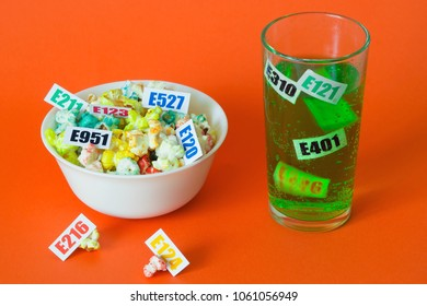 Harmful food additives. There are several tables with the code E-additives on the plate and in glass with green soda.