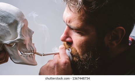 Harmful habits. Destroy your health. Smoking is harmful. Habit to smoke tobacco bring harm to your body. Smoking cause health damage and death. Man smoking cigarette near human skull symbol of death.