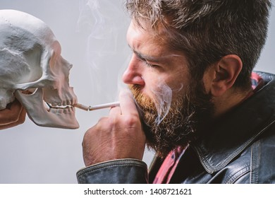 Harmful habits. Smoking is harmful. Habit to smoke tobacco bring harm to your body. Smoking cause health damage and death. Man smoking cigarette near human skull symbol death. Nicotine destroy health.