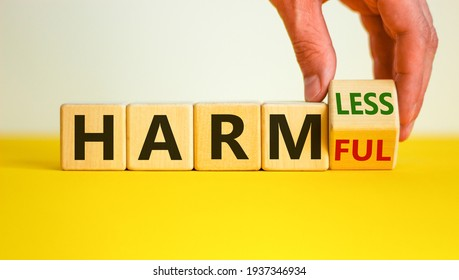 From harmful to harmless. Male hand turns the cube and changes word 'harmful' to 'harmless'. Beautiful yellow table, white background. Business and harmful or harmless concept. Copy space.