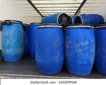 Harmful toxic chemical waste of MDMA or xtc heroïne in blue barrels or drums bin in van or truck. Garbage or waste dumped in nature or forest. Smuggling. Part of a serie.