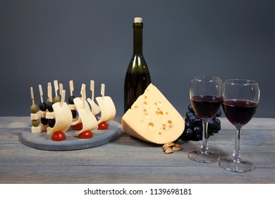 Harmonious composition bottle of red wine with two glasses, cheese, a bunch of grapes. Gastronomic products nicely laid out on wooden board. Isolated on gray background