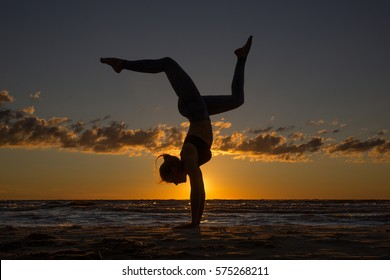 Harmonious landscape with a woman practicing yoga upside-down by the sea at sunset.