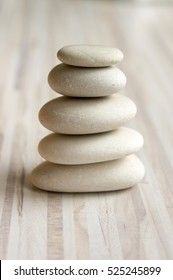 Harmony and balance, cairn, poise stones on striped table, rock zen sculpture, white and grey pebbles