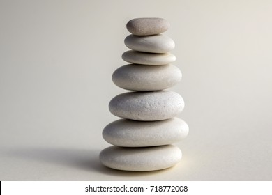 Harmony and balance, cairns, seven simple poise stones on white background, rock zen sculpture, white pebbles, single tower, simplicity