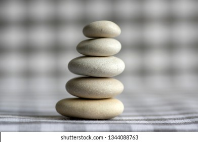 Harmony and balance, cairns, simple poise stones on white gray checkered background, rock zen sculpture, five white pebbles, simplicity