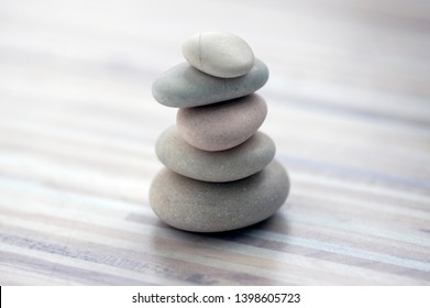 Harmony and balance, cairns, simple poise stones on wooden light white gray background, rock zen sculpture, five white pebbles, single tower, simplicity