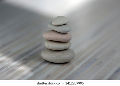 Harmony and balance, cairns, simple poise pebbles on wooden light white gray background, simplicity rock zen sculpture, river stones in towers