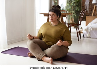 Harmony, balance, zen and peace concept. Indoor shot of plus size barefoot young brunette woman with hair bun sitting on mat keeping legs crossed and eyes shut, meditating after yoga practice