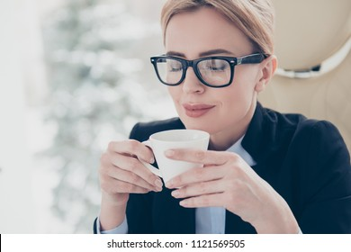 Harmony delight daydream concept. Close up portrait of calm pleased woman in eyeglasses holding cup with hot beverage in hands enjoying smell with close eyes