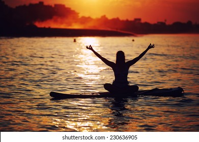 Harmony with the nature in yoga meditation, silhouette of woman doing paddle board yoga with beautiful orange sunset light reflected on the water, paddle surf yoga at the amazing sunset over the sea