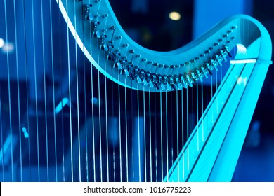 A harp bathed in blue neon light, waiting for an artist. Detail of a musical instrument.