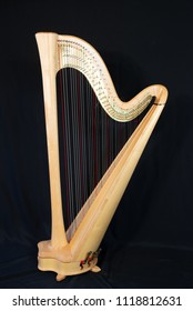 Harp musical instrument, isolated on a black background, vertically with copy space