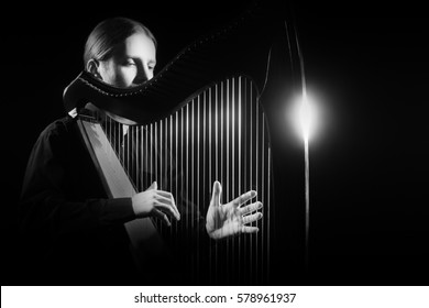Harp player. Classical musician harpist playing Irish harp music instrument isolated on black