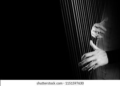 Harp player. Harpist hands playing Irish harp strings music instrument closeup