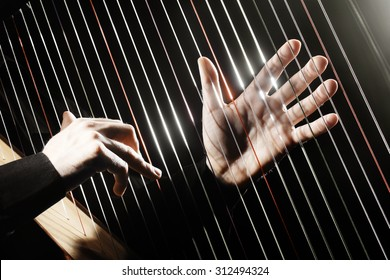 Harp strings closeup hands. Harpist with Classical Music Instrument