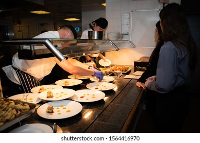 Harpenden, Hertfordshire/UK - November 7 2019: Chef prepares food at the pass whilst waiters stand by to deliver the food to the customers.