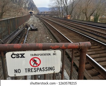 Harpers Ferry, WV / USA - December 8, 2018: A sign warns pedestrians from trespassing on CSX-owned railroad tracks that cross the Potomac River at Amtrak's passenger rail station.