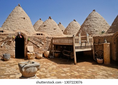HARRAN, TURKEY — MAY 3, 2011. A rake, old guns, decorative stone tablet, stone and clay pots, and a wood bed enhance the courtyard of a traditional mud-brick beehive house in Eastern Anatolia.
