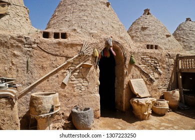HARRAN, TURKEY — MAY 3, 2011. A wood rake, rusty sword, old guns, decorative stone tablet, and stone and clay pots enhance the exterior of a traditional mud-brick beehive house in Eastern Anatolia.