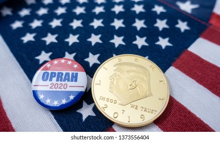 Harrisburg, PA - April 18, 2019 - Oprah 2020 Presidential campaign badge  and Donald Trump coin against US flag background. Close-up selective focus - image