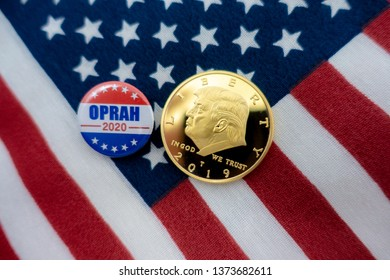 Harrisburg, PA - April 18, 2019 - Oprah 2020 Presidential campaign badge  and Donald Trump coin against US flag background - image