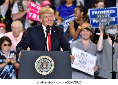 "HARRISBURG, PA - APRIL 29, 2017: President Donald Trump smiles during his celebration of 100 days in office. ""Promises Made, Promises Kept"" signs are visible."