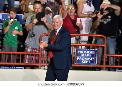 HARRISBURG, PA - APRIL 29, 2017: Vice President Mike Pence applauds as he arrives on stage at a Trump campaign rally marking 100 days in office at the Farm Show Complex and Expo Center.