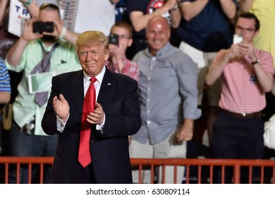 HARRISBURG, PA - APRIL 29, 2017: President Trump walks on stage to applause as he prepares to deliver a speech marking 100 days in office. Held at The Farm Show Complex and Expo Center.