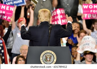 "HARRISBURG, PA - APRIL 29, 2017: President Trump turns around to give a ""thumbs up"" to supporters as he delivers a speech to mark 100 days in office. Held at The Farm Show Complex and Expo Center."